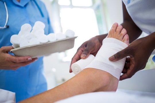 Doctor bandaging patients leg