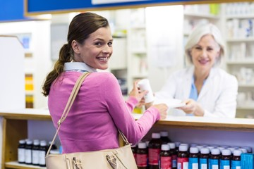 Smiling customer and pharmacist holding medicine in pharmacy