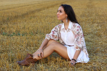 Beauty Romantic Girl Outdoors. Fashion boho style woman portrait, enjoy summer Lying on the Field in Sunset Light. Autumn.