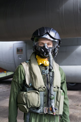 Figurine of fighter pilot in front of military plane. Mannequin is wearing flight suit - helmet, mask for breathing, overall, vest. Direct look