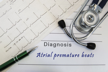 Diagnosis of Atrial premature beats. Stethoscope, green pen and electrocardiogram lie on medical form with diagnosis of Atrial premature beats on the desk in the office of cardiologist