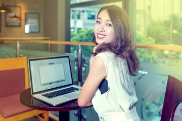 Asian business woman working on a laptop in cafe, smiling towards camera