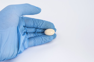 Soft gelatin vaginal tablet or suppository in the hand of the gynecologist, dressed in a blue latex glove. Treatment of diseases of the reproductive organs of women and prevention of women's health