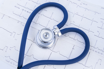 Heart formed stethoscope against background of electrocardiogram (ekg). Head or chestpiece and flexible tubing of blue stethoscope folded into heart shape, which lies on printed electrocardiogram