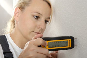 Handwerker mit Messgerät misst Feuchtigkeit in Wand von Haus