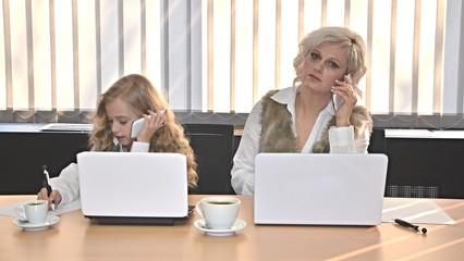 mother and daughter with laptops working in office