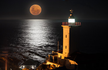 A full moon rising over the sea with a lighthouse in the foreground