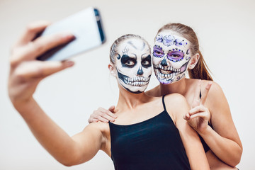 Two girls going on Halloween, grimace and make selfie Wall mural
