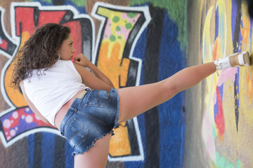 Pretty lady with curly hair wear a crop top shirt and shorts do a fight moves, graffiti wall as background