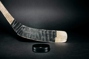 Old used ice hockey stick with puck