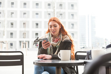 Woman looking at her phone at outdoor cafe