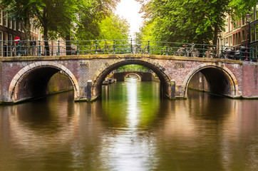 Old Bridge over a Canal in Amsterdam and Reflection in Water