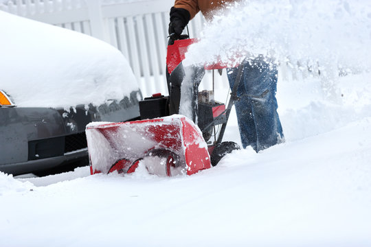 Snow blower clearing snow from driveway