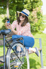 Take a selfie. Portrait of happy young woman using her mobile phone while sitting outdoor and relaxing.
