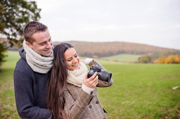Beautiful young couple with camera taking pictures. Autumn natur