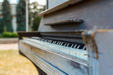 Old piano painted in blue color on the street