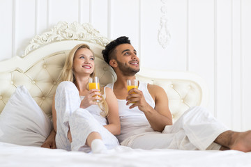 Young Couple Drink Orange Juice Sitting In Bed, Happy Smile  Hispanic Man And Woman Look Up
