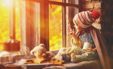 child girl with cup tea looking through window at nature autumn