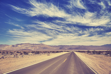 Vintage toned desert road in Death Valley with amazing cloudscape, travel concept, USA.