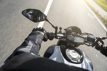 Motorradfahrer fährt auf Straße im Sommer