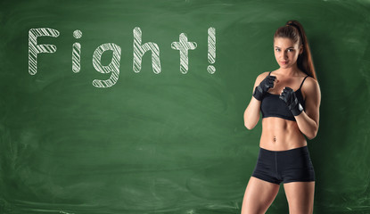 Fitness girl clenching her fists ready to fight on the background of a chalkboard