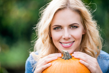 Close up, Beautiful young blond woman holding orange pumpkin