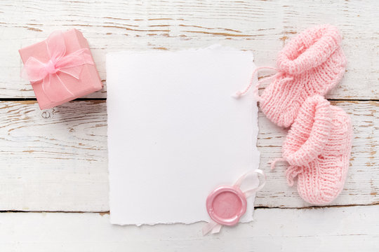 Baby girl clothes, blank card with wax seal and small present box on white wooden background. Flat lay. Owerhad view