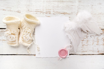 New Born or baptism Greeting Card. Blank with baby girl shoes and angel wings on white wooden background
