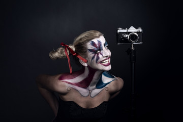 Woman in clown motley halloween make up costume with old photo camera