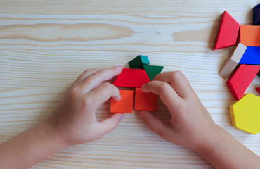 A child plays with colored blocks constructs a model on a light