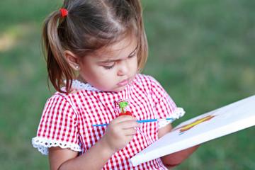 маленькая девочка рисует красками на природе