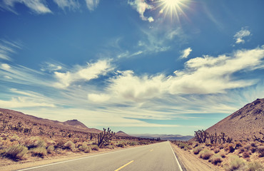 Vintage toned desert road against sun, travel concept.