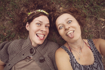 Two funny girls showing their tongues in nature