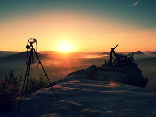 Tripod with running camera on  peak ready for photography. Sharp rocky peaks