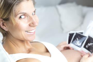 Portrait schwangere Frau liegend betrachtet Ultraschallbilder