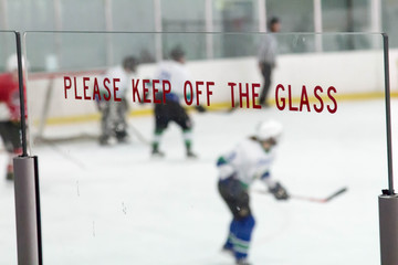 Please keep off the glass sign during a hockey game