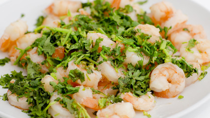 Fried shrimps with the greens. Easy seafood snack on white background close-up.