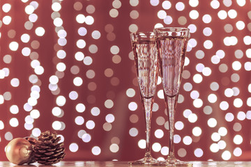 Wall Mural - Two glasses of champagne with Christmas toys. Festive lights bok