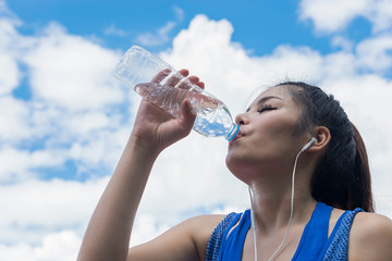 Asian girl sport fitness model in sporty running clothes.Drinking water.