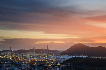 oil refinery with city on beautiful sunset background.