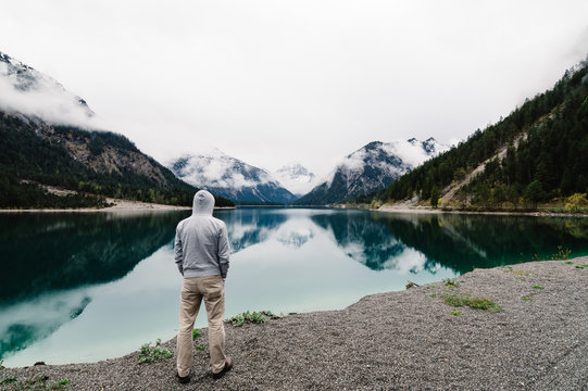Lonely man looking at mountain lake with  water reflections. Plansee lake located in Austria a cloudy and foggy day. Horizontal composition, space for copy