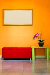 red stool chair, flowers on green table, and picture frame on orange wall