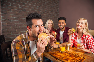 People Group Eating Fast Food Burgers Sitting At Wooden Table In Cafe
