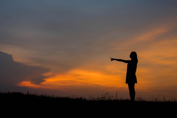 ilhouette young woman pointing forward to Dream ahead in sunset