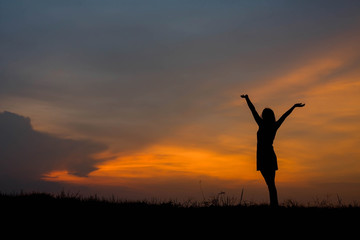 silhouette of woman  enjoys outdoor at sunset