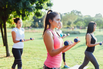Beautiful women group doing exercise with dumbbells