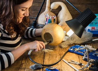 young woman working in artisan carving creative workshop