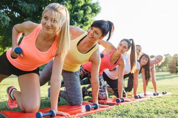 Beautiful sportswomen doing exercise in the park
