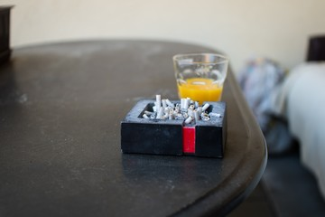 Ashtray full of pets and cigarette butts on the table