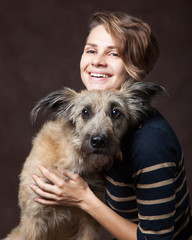 Beautiful young woman with a funny shaggy dog on a dark backgrou